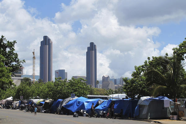 People camp out on a sidewalk in the Kakaako neighborhood of Honolulu. A Hawaii lawmaker wants to classify homelessness as a medical condition so that people could use Medicaid money for rent payments. (Audrey McAvoy/AP)