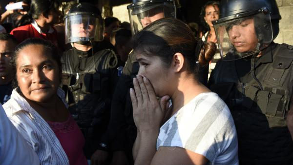Relatives gather outside the Virgin of the Assumption Safe House near Guatemala City, Guatemala. Dozens of girls died after a fire broke out at the youth shelter on Wednesday.
