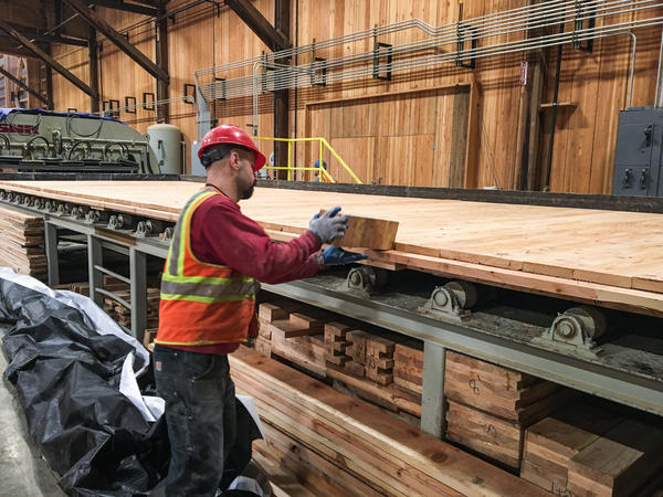 D.R. Johnson's Steve Allen uses a block of wood to make sure boards are aligned properly before the CLT panel enters the pressing machine at far left.