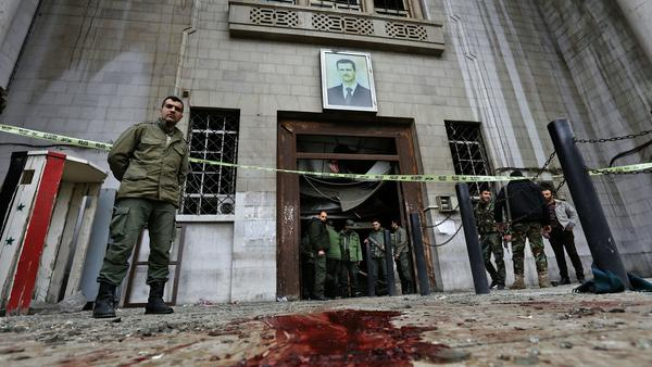 Syrian security forces gather under a portrait of President Bashar Assad at the Palace of Justice in Damascus following a suicide bombing on Wednesday.