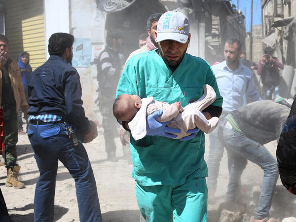 A Syrian health worker in Aleppo carries a baby injured during the an air strike by Syrian regime forces.