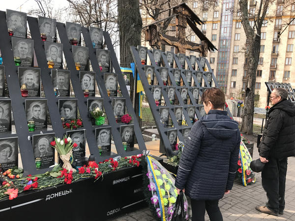 Passersby pay tribute to activists who were killed during 2014 anti-government protests near the Maidan, Kiev's main square.