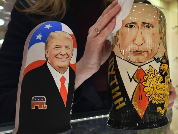 An employee at a Moscow gift shop polishes traditional Russian wooden nesting dolls depicting Donald Trump and Russian President Vladimir Putin.