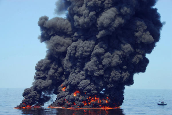 Black smoke billows from a controlled burn of surface oil during the 2010 Deepwater Horizon oil spill.