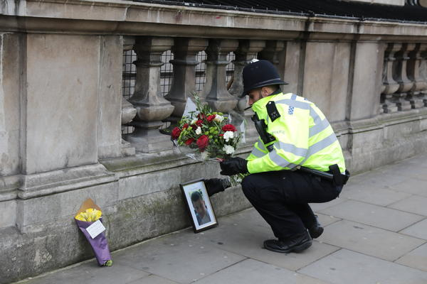 """A police officer places flowers from a member of the public next to a photo of Keith Palmer, the police officer who was stabbed Wednesday as he guarded the Palace of Westminster. Prime Minister Theresa May said of Palmer, """"He was every inch a hero."""""""