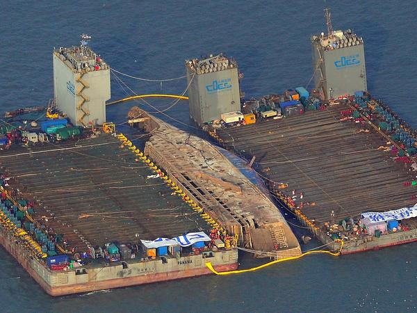 This aerial image shows part of the damaged Sewol ferry between two barges during a salvage operation Thursday.