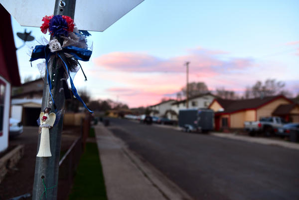 An angel and flowers are tied to a stop sign on the corner of West Clay Avenue in Flagstaff, near the location where Stewart was shot.
