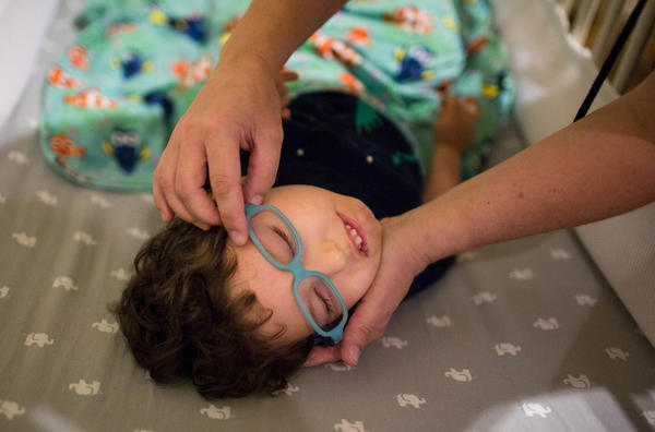 Kathleen helps her son Gideon get his glasses on. Part of Gideon's brain was damaged during development, which effects his vision.