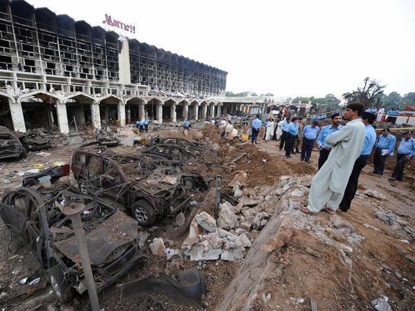 Pakistani security officials gather outside the devastated Marriott Hotel in Islamabad on Sept. 21, 2008, following an overnight suicide bomb attack. The Pentagon announced Satuday that a recent airstrike had killed Qari Yasin, who was linked to the bombing.
