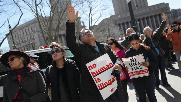 Local officials are promising a legal fight in the face of a block on grants from the Justice Department over immigration enforcement. Here, protesters pray outside the Immigration and Customs Enforcement office in New York City this month.