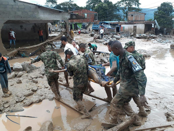 Soldiers carry a victim on a stretcher in Mocoa, Colombia, on Saturday, after an avalanche of mud and water from an overflowing river swept through the city as people slept. The incident triggered by intense rains left at least 125 people dead.
