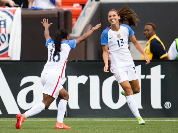 Crystal Dunn (left) celebrates with Alex Morgan after Morgan scored during a friendly match against Japan last year. The World Cup champion team and the U.S. Soccer Federation have settled on a wage deal, ratifying a contract that runs through 2021.