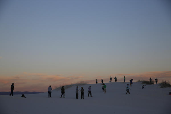 Park visitors watch as the sun sets over White Sands.