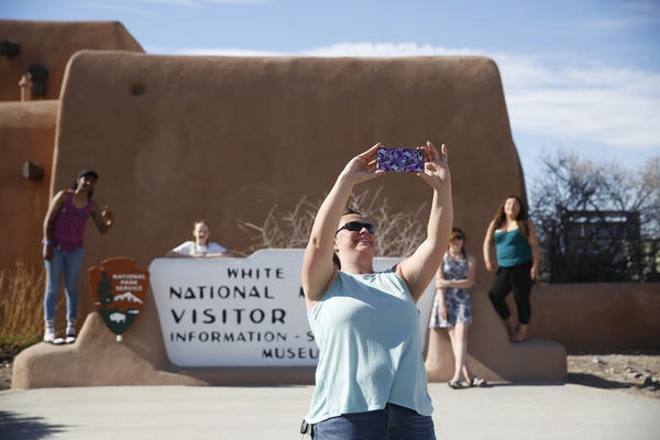 Tourists take photos outside the entrance of White Sands National Monument in New Mexico.