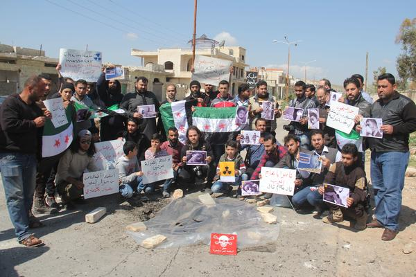 Syrian residents of Khan Shaykhun hold signs and pictures on Friday during a protest condemning a suspected chemical weapons attack on their town earlier this week.