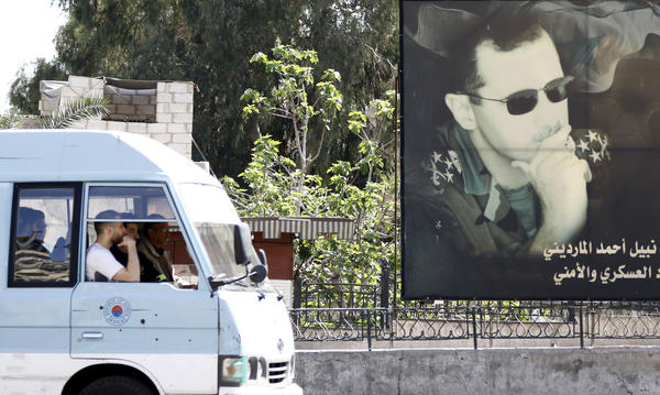 """A minivan drives past a portrait of Syrian President Bashar Assad in Damascus last week. U.S. forces fired a barrage of cruise missiles at a Syrian air base Thursday in response to what President Trump called a """"barbaric"""" chemical attack he blamed on the Assad regime."""