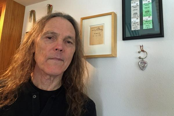 Schmit stands in front of a framed note from Eagles bandmate Glen Frey. (Robin Young/Here & Now)