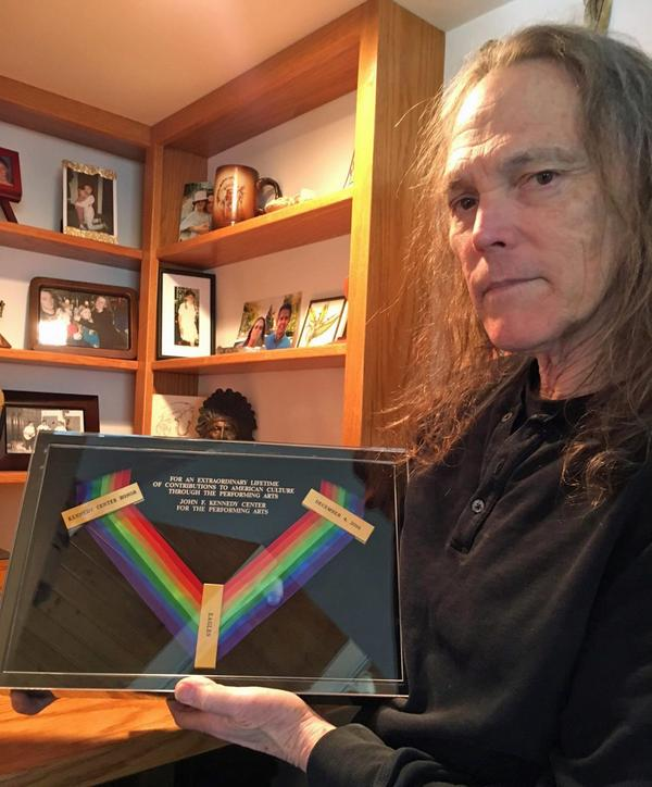 Schmit holds the Kennedy Center Honors medal won posthumously by Eagles bandmate Glenn Frey. (Robin Young/Here & Now)