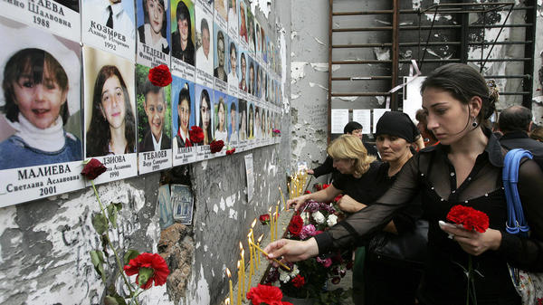 A lack of official coordination and the use of powerful weapons contributed to the casualties during a terrorist takeover of a school in Beslan, Russia, in 2004, a European court says. Here, people lay flowers and light candles at the school gym in 2009, marking the fifth anniversary of the attack.