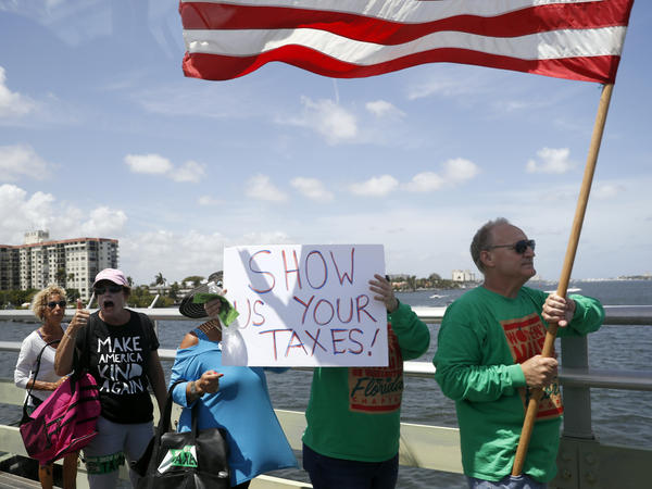 Protesters walk during a rally to encourage the release of President Donald Trump's tax returns on Saturday, April 15, 2017, in Palm Beach, Fla.