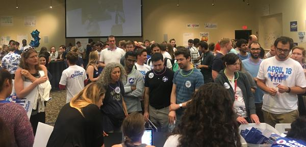Supporters at an election eve rally for Democrat Jon Ossoff line up to get canvassing packets.