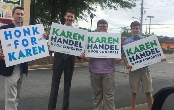 Supporters for Republican Karen Handel wave signs along a highway in Sandy Springs, Ga.