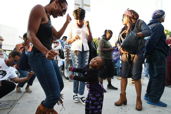 People dance to Prince's music at Leimert Park in Los Angeles where fans gathered to celebrate and remember the pop music icon's life on April 21, 2016.