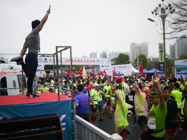 A trainer guides marathoners in a series of stretches before the start of the race.