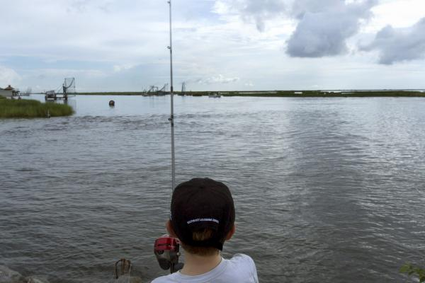 A boy fishes on a bayou near Isle de Jean Charles, La., in August 2015. Louisiana is still losing about a football field of coastline every hour.