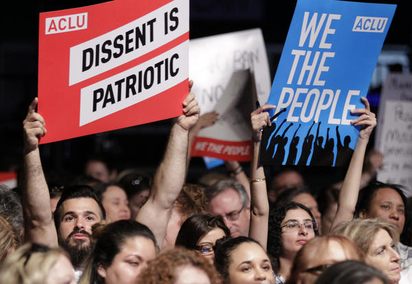"""Protesters hold up signs during a meeting called """"The Resistance Training"""" hosted by the American Civil Liberties Union in March."""