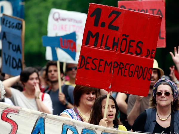 "A young girl holds a sign with the words ""1.2 Million Unemployed"" during an anti-austerity protest in Lisbon on May 12, 2012."