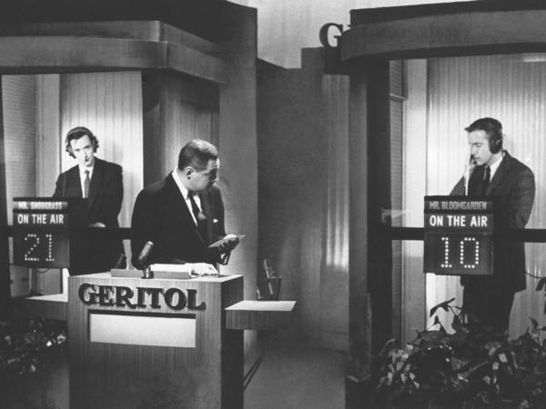 Host Jack Barry conducts questioning of contestants James Snodgrass (left) and Hank Bloomgarden (right) in supposed isolation booths during the program <em>Twenty-One</em>. Albert Freedman, producer of the show, died on April 11 at age 95.