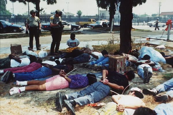 Police stand over a group of handcuffed looting suspects in Los Angeles on April 30, 1992, as rioting continued throughout the area.