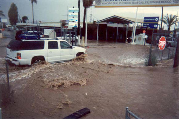 Blocked by the pedestrian fence, floodwaters from Headquarters Wash near Lukeville, Ariz., flowed along the fence and into the Mexican Port of Entry in Sonoyta, Sonora, in 2008.
