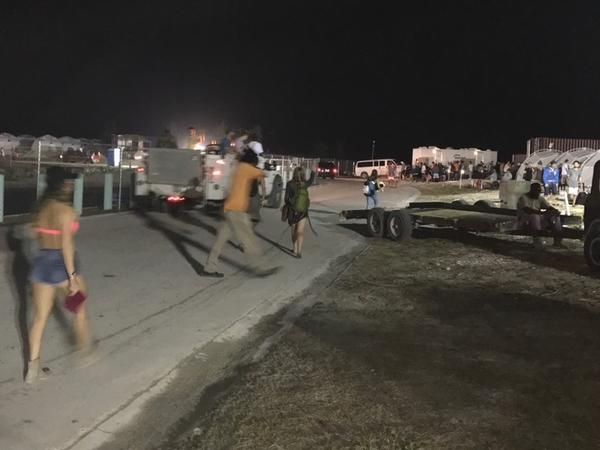 Fyre Festival attendees walk around the event site on Thursday night in Grand Exuma, Bahamas. Festivalgoers had paid thousands of dollars for villas and lodges on the beach, but instead found a chaotic tent city.