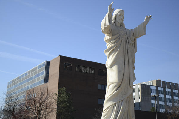A statue of Jesus watches over Fort Wayne. Behind it: the offices of Fort Wayne Community Schools.