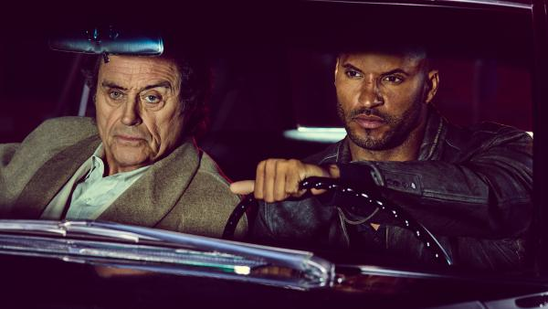 Ian McShane as Mr. Wednesday and Ricky Whittle as Shadow Moon hit the road in the new Starz adaptation of Neil Gaiman's <em>American Gods.</em>