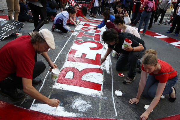 Protesters paint a mural on the street during a May Day demonstration outside of a U.S. Immigration and Customs Enforcement office in San Francisco, Calif.