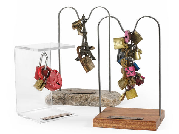 """A collection of """"love locks"""" available for auction that will benefit three charities that aid refugees. The auction's appraiser estimates that prices will range from 150-200 euros ($163-218) for a cluster of padlocks."""