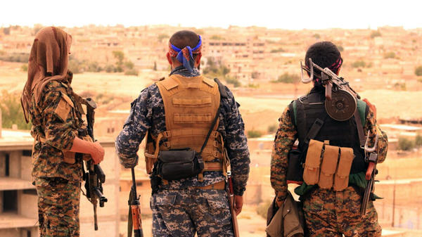Members of the Syrian Democratic Forces look toward Tabqa, Syria. The U.S. announced Tuesday that it will begin arming Kurds allied with the SDF as the Pentagon prepares an offensive to retake the ISIS stronghold Raqqa.