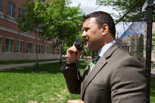 Pankaj Rayamaji speaks through his trusted walkie-talkie to a teacher inside. Rayamaji is the director of logistics and operations at Columbia Heights Education Campus in Washington, D.C.
