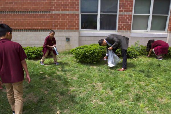 """Rayamaji enlists the help of a few middle schoolers to pick up trash. """"It blows in off the street,"""" he says."""