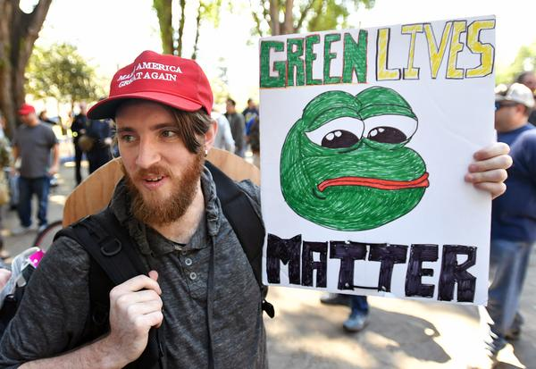 Andrew Knight holds a sign of Pepe the frog, an alt-right icon, during a rally in Berkeley, Calif., on April 27.