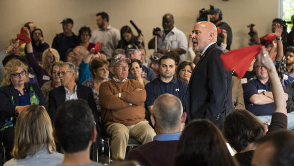 Audience members wave red flags in response to Rep. Tom MacArthur, R-N.J., at a raucous town hall Wednesday night in Willingboro.