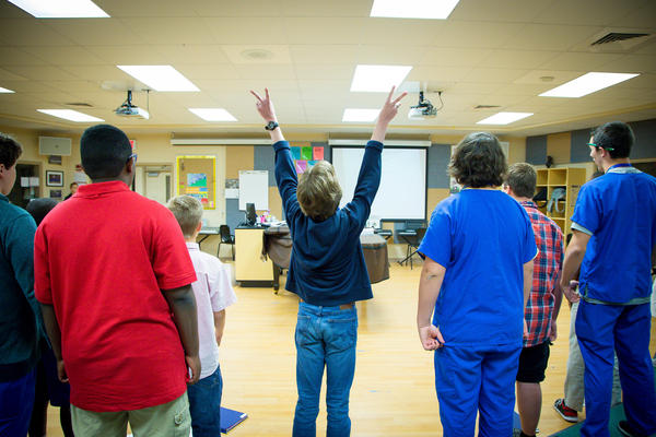 Reed (center) enthusiastically raises two peace signs while singing a tune from the Broadway musical <em>Newsies</em> during Ashley Leland's boys' chorus class at Jupiter Middle School of Technology in Jupiter, Fla.