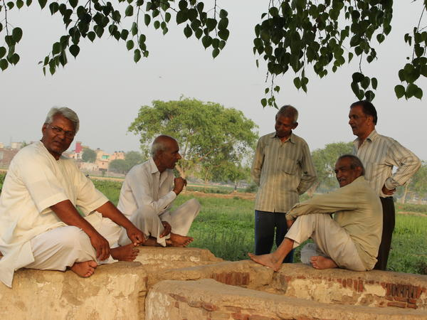 Indian farmers talk beneath a fig tree. Since people couldn't use cash, many farmers couldn't sell their crops.