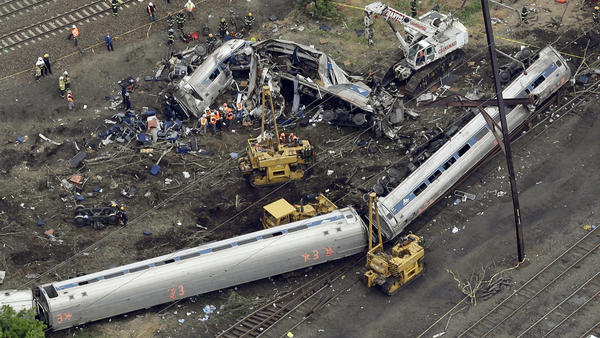 Emergency personnel work at the scene of a deadly Amtrak derailment in Philadelphia in 2015. The engineer has been charged with crimes including involuntary manslaughter.