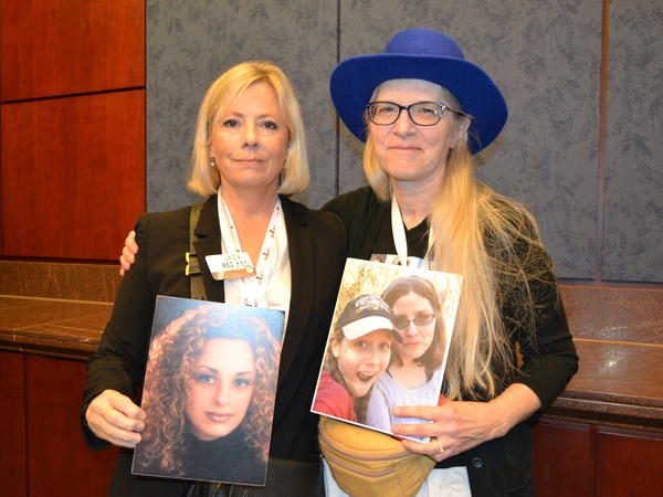 Lois Durso (left) holds a picture of her daughter, Roya. Marianne Karth (right) holds a picture of her daughters, AnnaLeah and Mary.