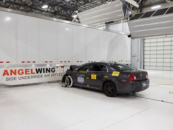 In this April 2017 photo provided by the Insurance Institute for Highway Safety, during a 35 mph crash test, a steel and fiberglass underride guard prevents a car from going underneath a tractor-trailer.