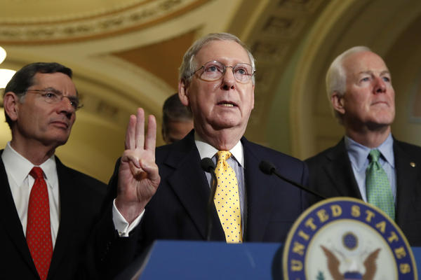 Senate Majority Leader Mitch McConnell is flanked by Sen. John Barrasso, R-Wyo., (left) and Senate Majority Whip John Cornyn of Texas (right).  They are three of the 13 senators in the health care working group.